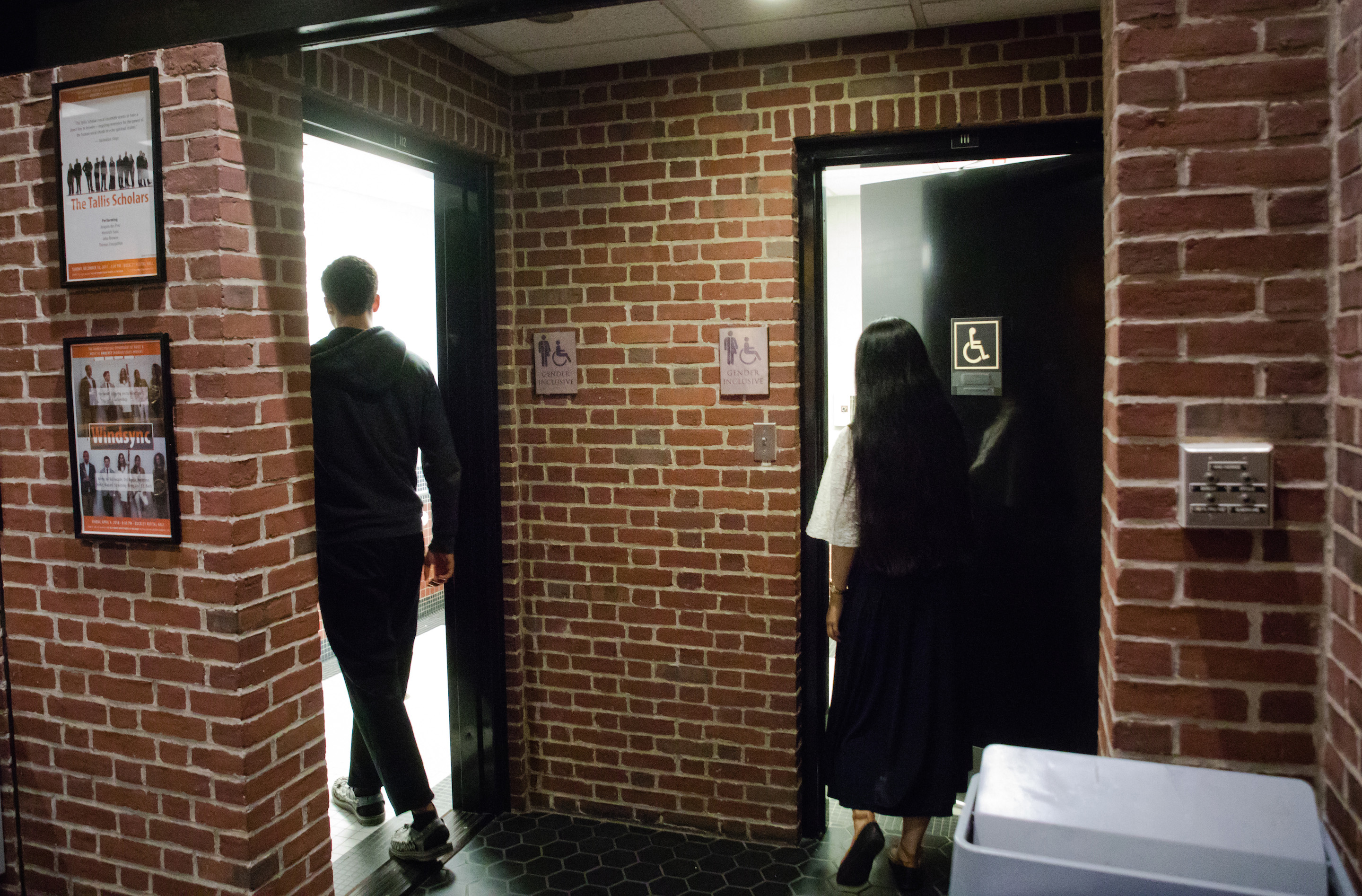 Two students open the door to newly converted gender-inclusive restrooms.