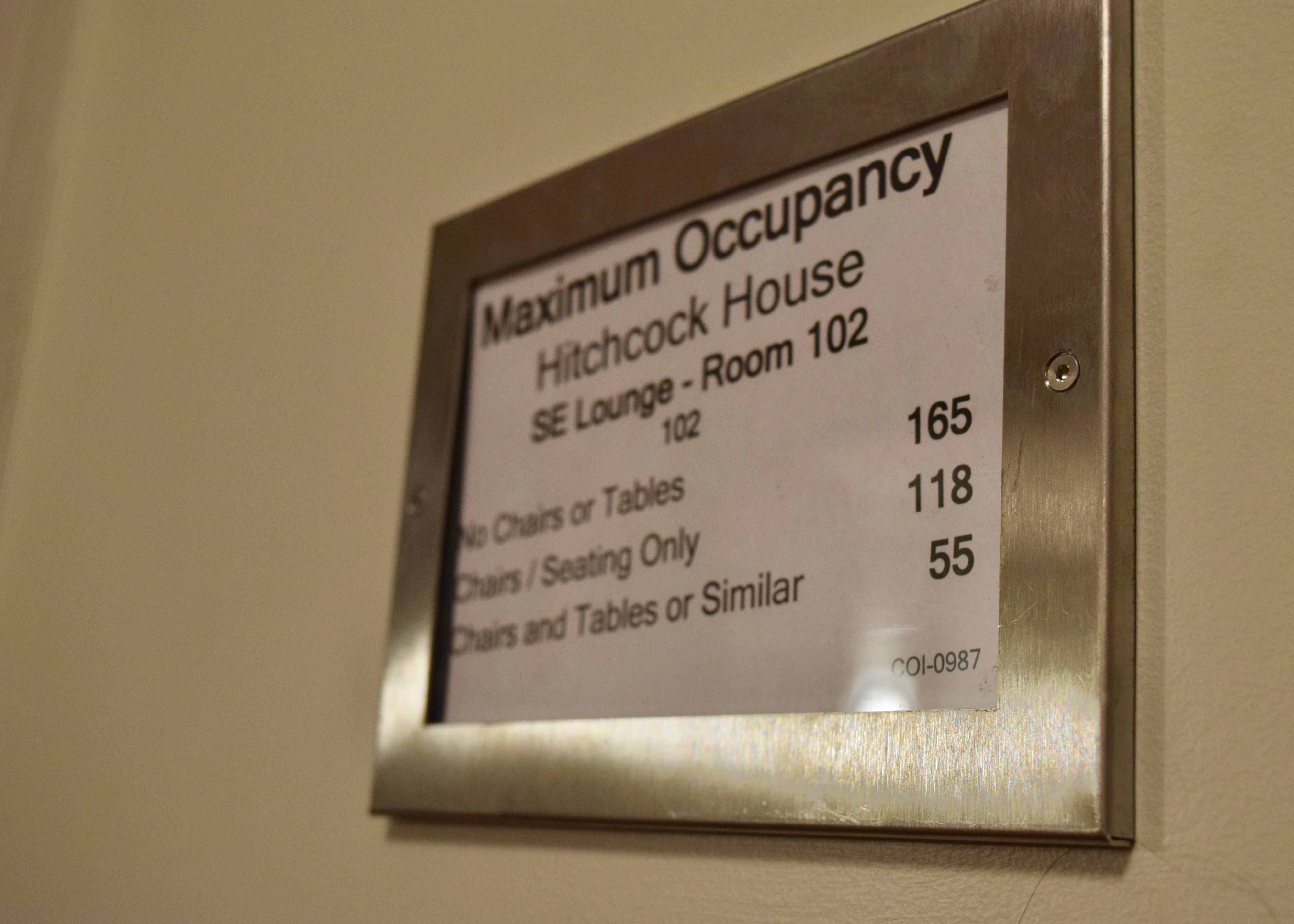 "A frame on the wall posts the maximum occupancy in the SE Lounge, or Room 102, for Hitchcock House: ""No Chairs or Tables — 165,"" ""Chairs/Seating Only — 118"" and ""Chairs and Table or Similar — 55."""